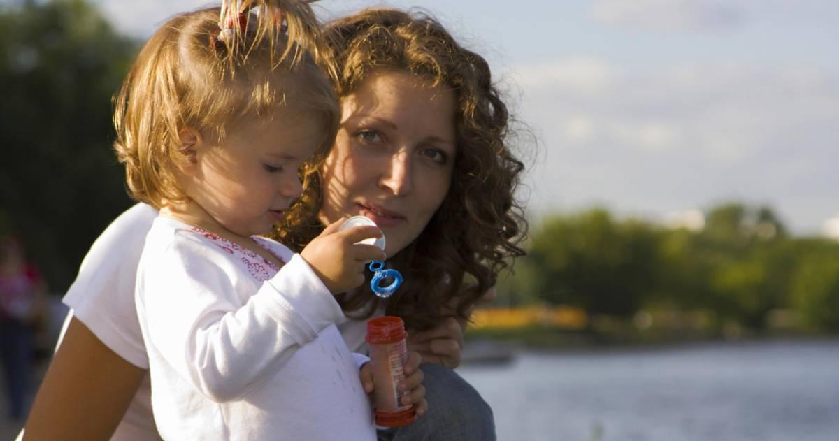 Vrouw staat buiten met kind in armen